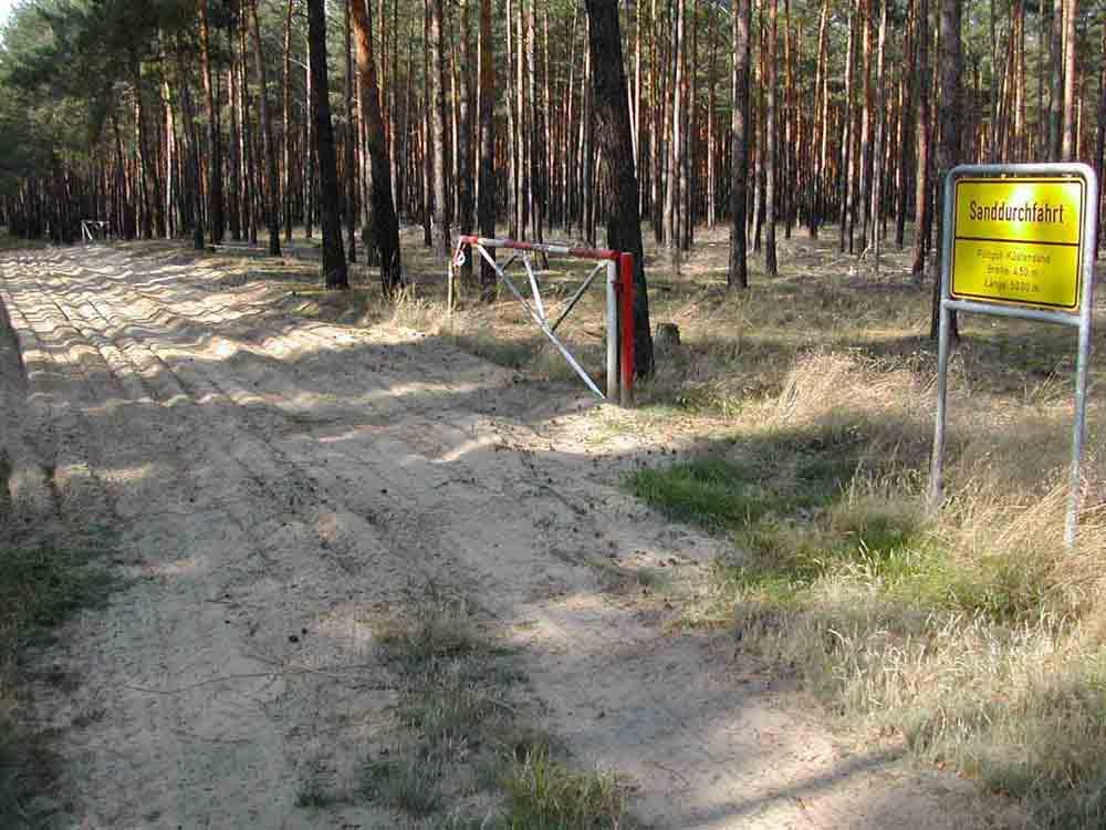 Sanddurchfahrt (Breite: 4,5 m, Länge: 50 m); Füllgut: 1 Gew.-% Schluff (Korngröße < 0,063 mm), 44 Gew.-% Feinsand (Korngröße 0,063-0,2 mm), 52 Gew.-% Mittelsand (Korngröße 0,2-0,63 mm), 3 Gew.-% Grobsand (Korngröße 0,63-2 mm).